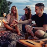 young friends camping on beach gather around fire and roast marshmellows