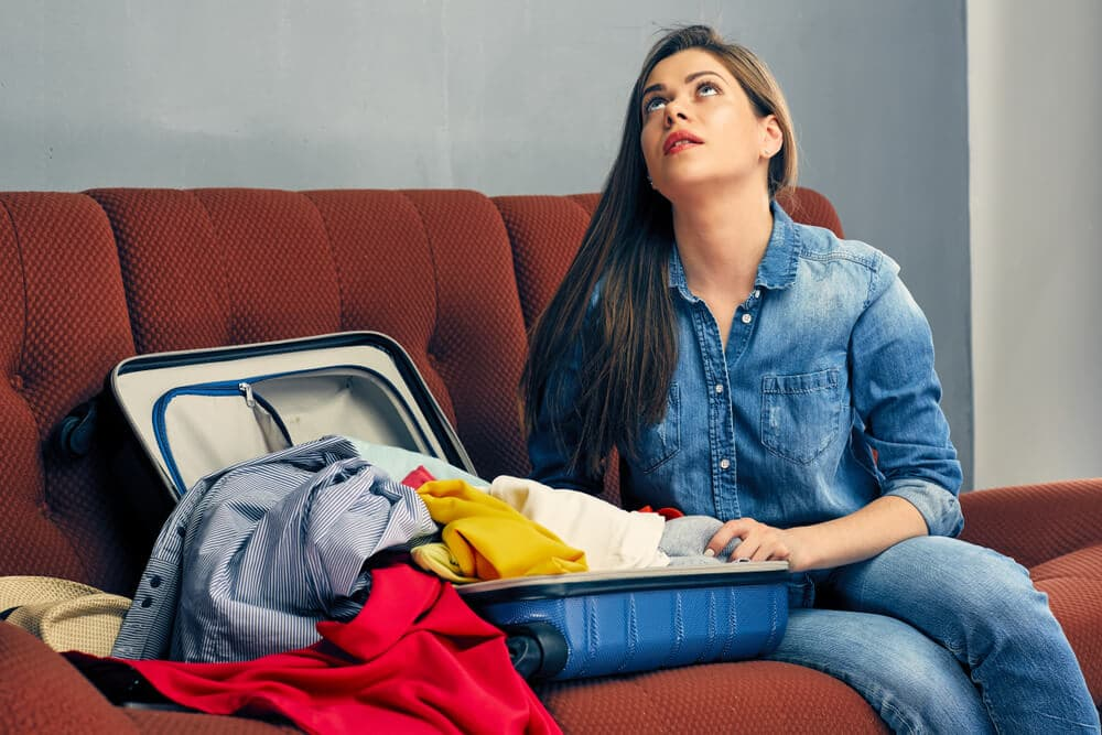 stressed woman packing suitcase