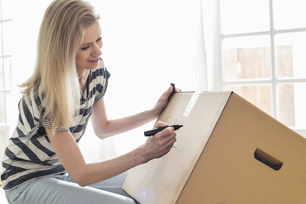 blonde woman labeling moving box