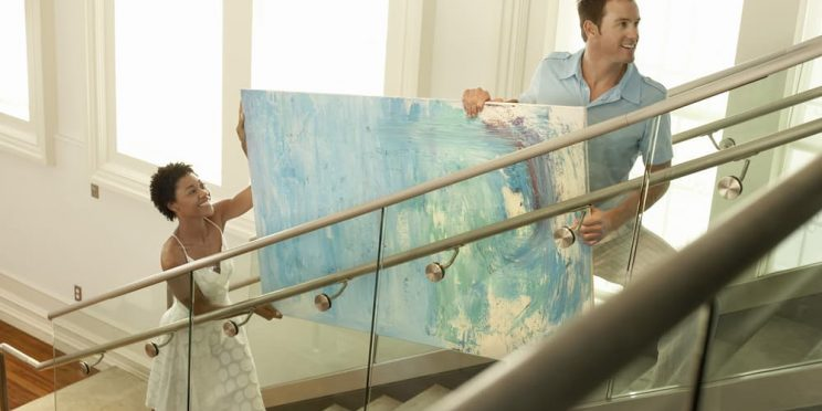 people carrying canvas art