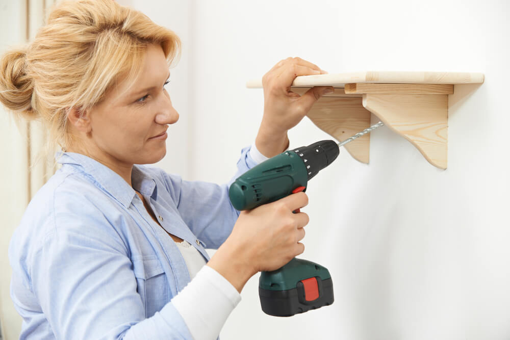 woman installing floating shelf