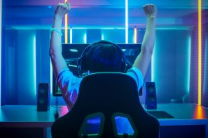 gamer in neon lit room desk