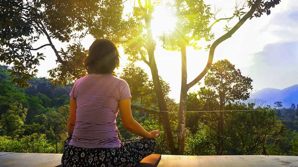 woman meditating outside by tree