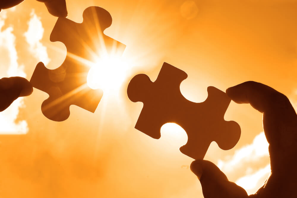 man holding puzzle pieces in sunlight