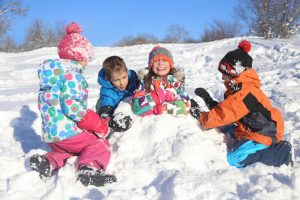 young children playing together in snow