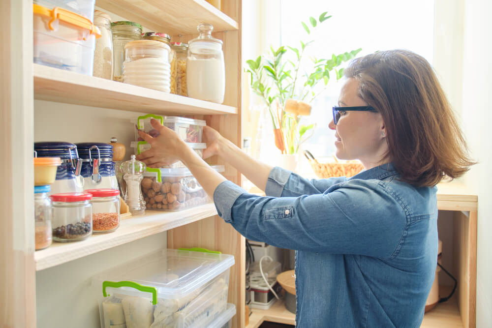 woman arranging pantry for orderliness