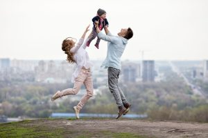 young happy family jumping for joy in front of a city skyline