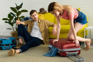 young couple packing many belongings into suitcase to move
